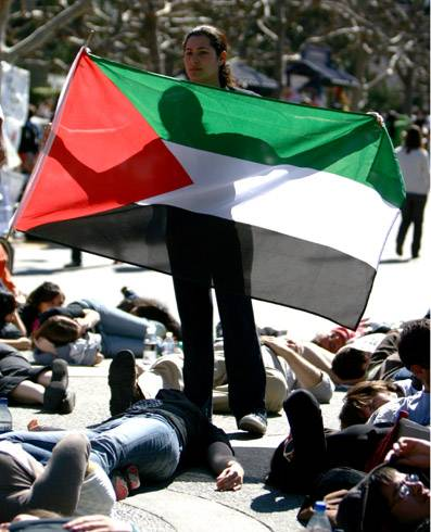 Photo: Tala Khanmalek grasped a Palestinian flag as she stood above fellow protesters who were lying on the ground on Lower Sproul Plaza yesterday afternoon to symbolize casualties of the Israeli-Palestinian conflict.