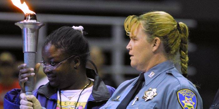 Photo: Participant Titor Sandee (left) and Ann Taglieri from the Vacaville Police Department watch as the torch is lit during the Special Olympics Opening Ceremony Friday evening at Haas Pavilion. This year, the games drew more than 900 athletes.