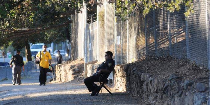 Photo: A police officer sits in front of a fence built around the tree-sit. Yesterday's court decision will allow the beginning of construction-and the removal of the Oak Grove.