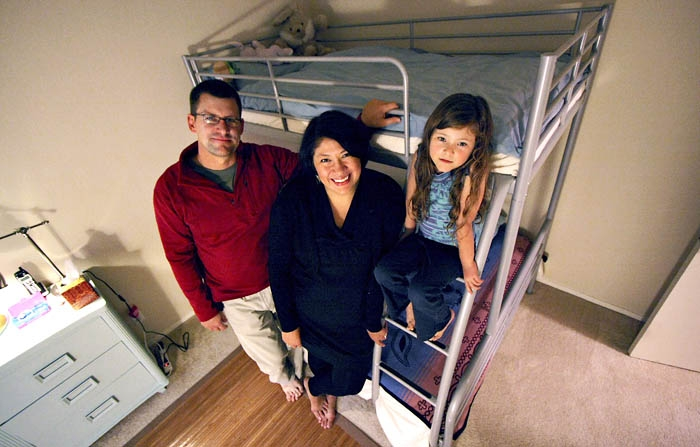 Photo: Professor Kimberly TallBear poses with her family in their apartment in Oakland. TallBear, like many UC Berkeley associate professors, could not afford housing in Berkeley.