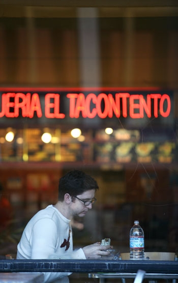 Photo: A patron of Taqueria El Tacontento, one of the current vendors in the Bear's Lair, enjoys a burrito. The food court's tenants will need to place bids to continue their leases.