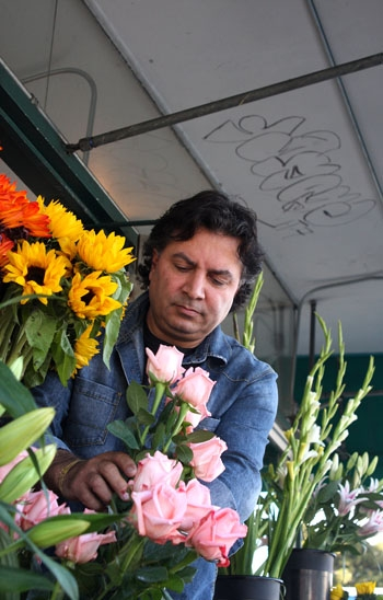 Photo: Iraj Misaghi, an owner of Ashby Flowers, arranges roses. The 50-year-old shop, located in what is now the Whole Foods Market parking lot, may close as Whole Foods did not renew its lease. A protest was staged on behalf of the shop. See page 2 for the story.