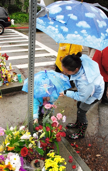 Photo: Community members place flowers at a memorial for Zachary Cruz, a 5-year-old boy who was killed in a traffic accident while walking to an after-school program.