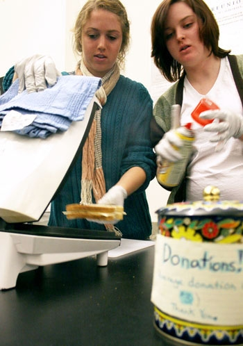Photo: Students Stephanie Ulrich (left) and Eryn Trowbridge make and sell grilled cheese sandwiches on campus to help raise money for the FeelGood club.
