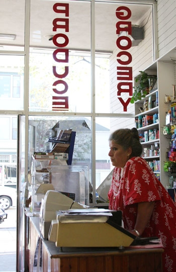 Photo: <b>Muna Ayyad</b> waits for customers at the cash register of Fred's Market on University Avenue. The market and deli serves over 30 Berkeley High School students a day.