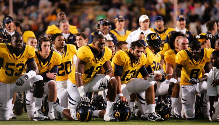 Photo: <b>The Cal football team</b> takes a knee and watches on as tailback Jahvid Best is attended to by medical staff. Best was released from the Highland General Hospital yesterday morning.