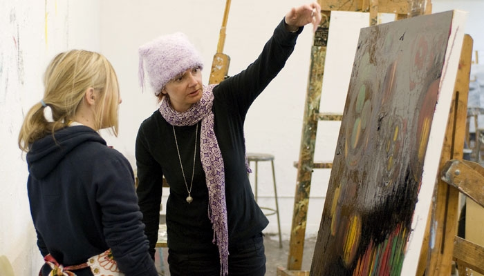 Photo: <b>Substitute professor Indira Morre</b> consults junior art practice major Erica Rosen on her work for an advanced painting class.