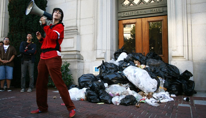 Photo: Demonstrators dumped a five-foot tall mound of trash bags outside the entrance of California Hall to protest university staff layoffs.