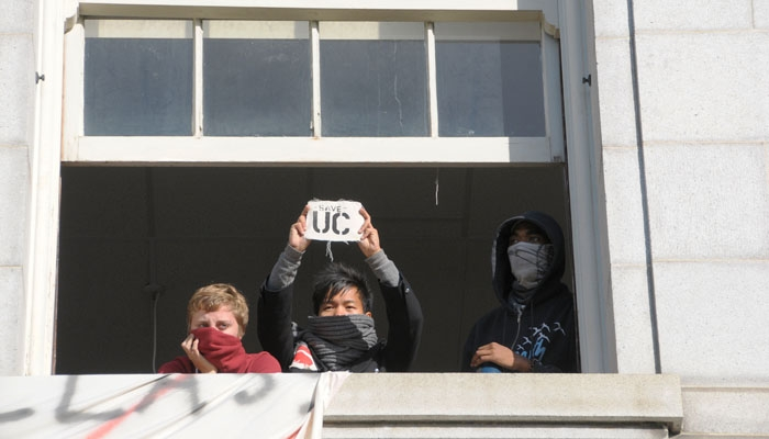 Photo: Protesters occupied a section of the second floor of Wheeler Hall early Friday morning. Throughout the day, they communicated their demands to those below through a window.