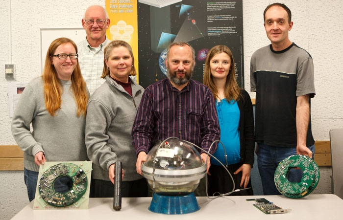 Photo: Lisa Gerhardt, Robert Stokstad, Sandra Miarecki, Spencer Klein, Mariola Lesiak-Bzdak and Thorsten Stezelberger (left to right) show off IceCube, a device intended to detect for neutrinos from the South Pole.