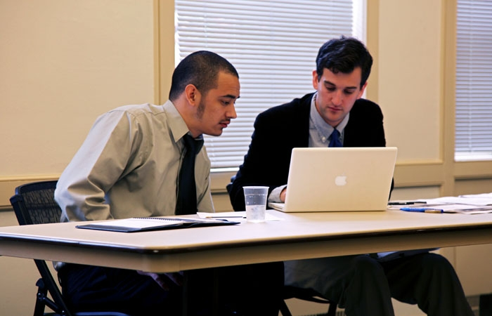 Photo: Julian Martinez, a senior facing misconduct charges, confers with law student Thomas Frampton at the student conduct hearing held Feb. 18.