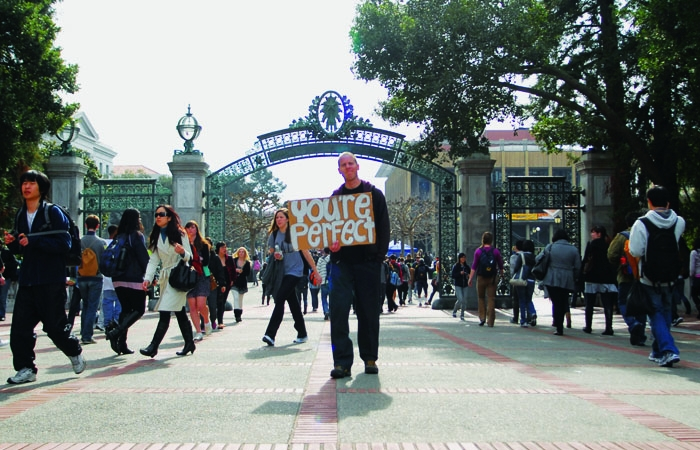 Photo: Benjamin Smythe holds up a sign in front of Sather Gate in an attempt to fulfill his personal quota of making one person smile every day.