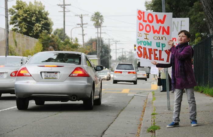 Photo: Nora Dolin holds a sign at Malcolm X Elementary School during a rally to promote careful driving and pedestrian safety.