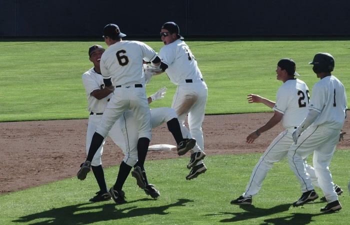 Photo: The Bears mob freshman Michael Theofanopoulos after his walk-off double.